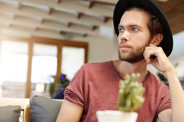 Foto de cabeza de hombre joven de moda con barba con sombrero elegante con expresión pensativa mientras pasa la mañana en un restaurante acogedor, esperando su café y haciendo planes para el día