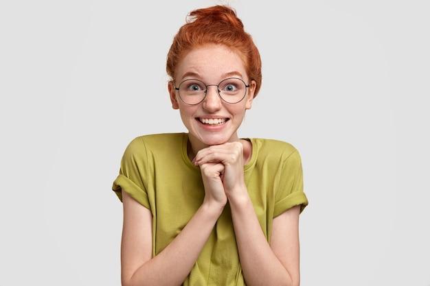 Foto de cabeza de una mujer bonita pelirroja que mira con felicidad, mantiene las manos debajo de la barbilla, anticipa sorpresa preparada por el novio, usa gafas ópticas redondas, camiseta casual, aislado en blanco