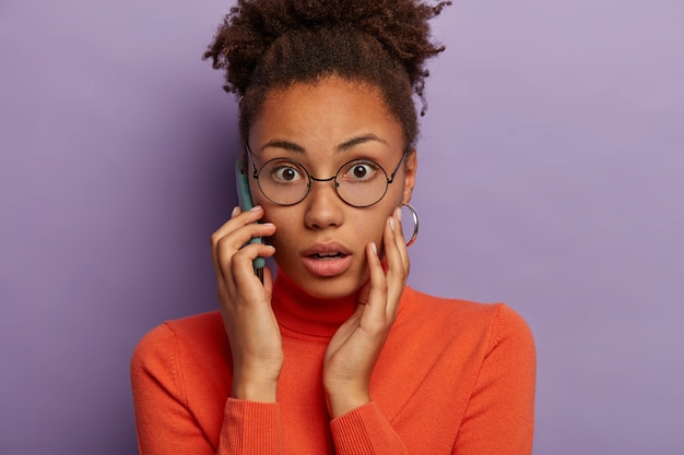 Foto de cabeza de una mujer de piel oscura emocional atónita que jadea de miedo, escucha noticias desagradables, tiene una conversación telefónica, usa lentes ópticos y cuello alto, modelos sobre fondo púrpura.