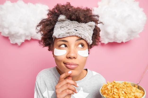 Foto de cabeza de una mujer rizada soñadora reflexiva mantiene la mano en la barbilla se ve pensativa a un lado vestida en pijama tiene un desayuno saludable sostiene un tazón de copos de maíz hace planes para el día de trabajo