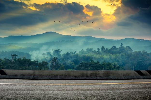 Una foto de la carretera con puesta de sol. paisaje en el horario de verano en tailandia.