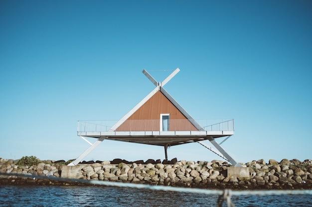 Foto de una casa en forma de triángulo frente al agua bajo un cielo azul