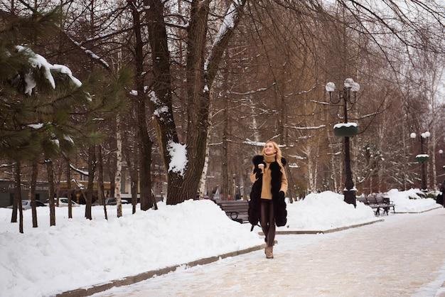 Foto de cerca al aire libre de joven hermosa mujer sonriente feliz caminando en la calle en invierno.