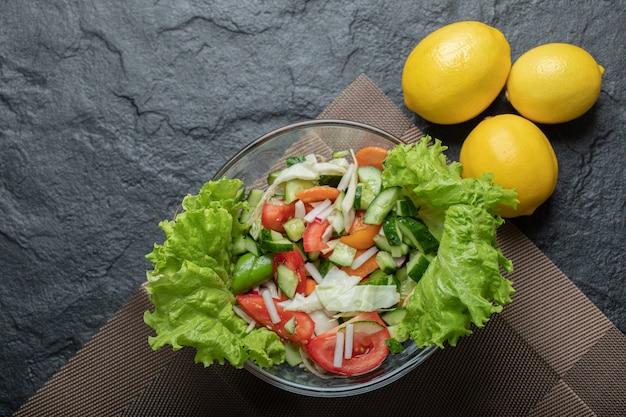 Foto de cerca de ensalada de verduras saludables con limón sobre fondo negro. foto de alta calidad