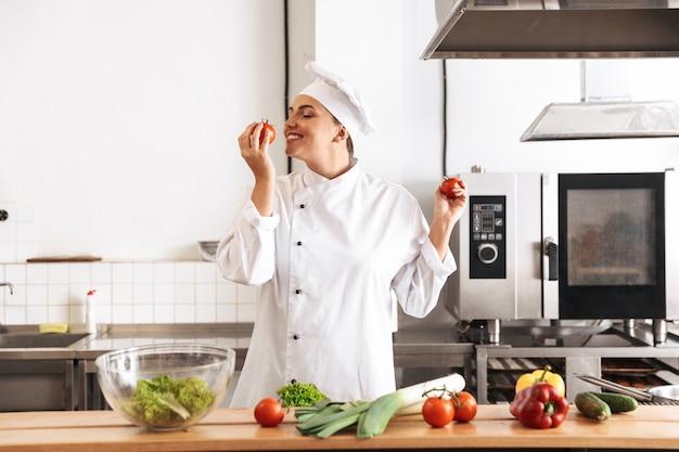 Foto de chef mujer complacida vistiendo uniforme blanco cocinar comida con verduras frescas, en la cocina del restaurante