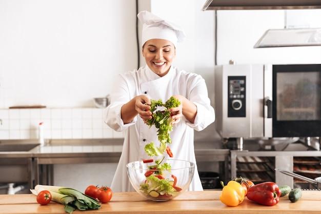 Foto de chef mujer complacida vistiendo uniforme blanco haciendo ensalada con verduras frescas, en la cocina del restaurante