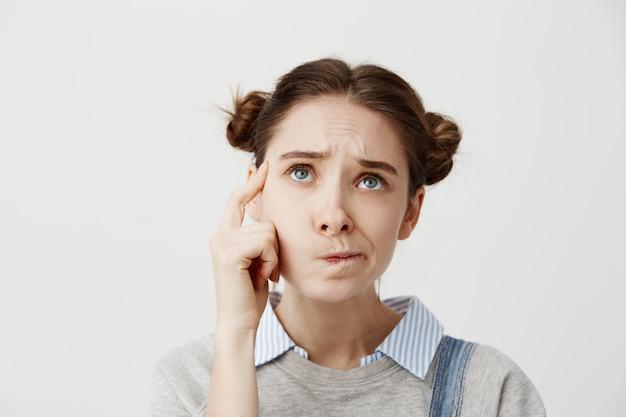 Foto de chica adulta mirando hacia arriba con el ceño fruncido expresando malentendido. linda estudiante torciendo la boca tratando de recordar su horario o molestarse por los exámenes.