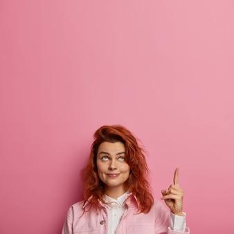 Foto de una chica guapa, mira y señala hacia arriba, da consejos o muestra hacia arriba, tiene una sonrisa tierna, piel sana