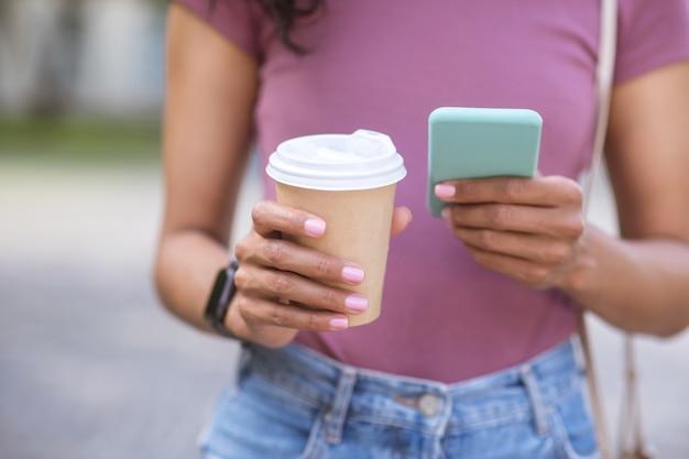 Foto. una chica haciendo la foto de una taza de café en un smartphone