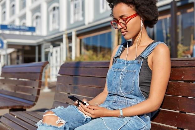 Foto de chica hipster de piel oscura, corte de pelo afro, chatea con seguidores en redes sociales, escucha música favorita en auriculares, pasa tiempo libre al aire libre, se sienta en un banco de madera, espera a un amigo