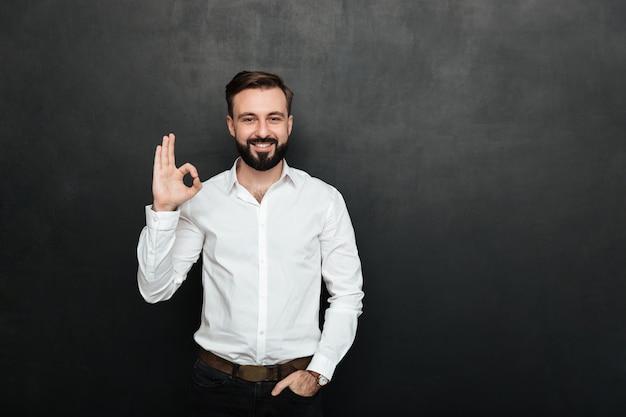 Foto de un chico sin afeitar en la oficina sonriendo y gesticulando con un signo ok expresando que todo está bien, aislado sobre grafito