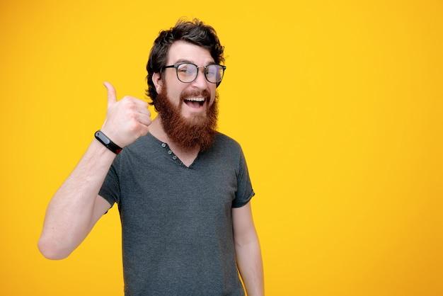 Foto de chico alegre con barba en gafas, está mostrando el pulgar hacia arriba en amarillo