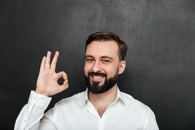 Foto de chico barbudo sonriendo y gesticulando con un signo ok expresando una buena elección, aislado sobre grafito