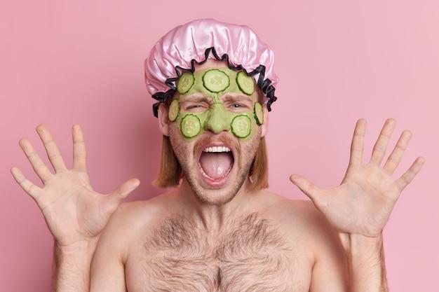 Foto de chico emocional mantiene las palmas levantadas exclama en voz alta aplica mascarilla verde con pepinos se somete a tratamientos de belleza usa gorro de baño.