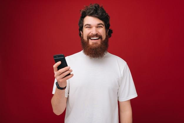 Foto de chico feliz bearde sosteniendo un móvil y sobre pared roja