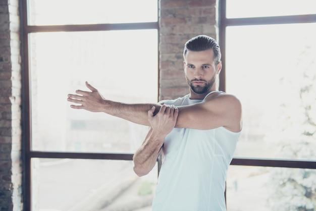 Foto de chico guapo con barba preparándose para el entrenamiento matutino estiramiento calentando los músculos de la mano ropa deportiva pantalones cortos sin mangas zapatillas de deporte casa de entrenamiento grandes ventanas en el interior