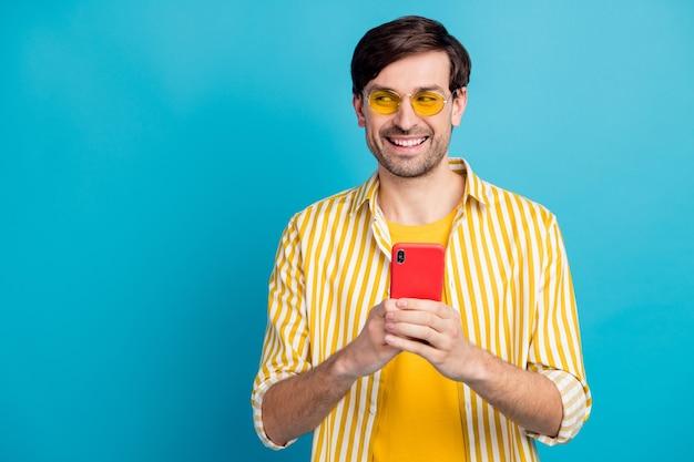 Foto de chico positivo, uso turístico, smartphone, look, copyspace, disfrute, red social, blog, instagram, vacaciones, post, uso, blanco, estilo, amarillo, ropa, aislado, azul, color, plano de fondo