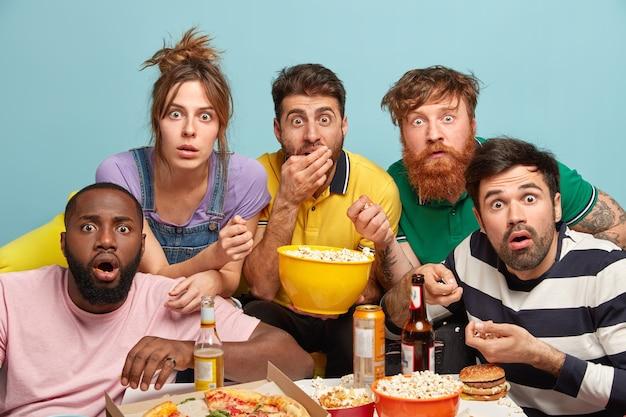 Foto de cinco mujeres y hombres de raza mixta ven una película de suspenso, noticias horribles, miran con pánico, comen palomitas de maíz, miran fijamente con ojos saltones, aislados sobre una pared azul, tienen miedo. película de miedo en casa