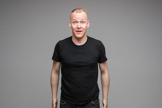 Foto de cintura para arriba del hombre emocional en negro abriendo la boca