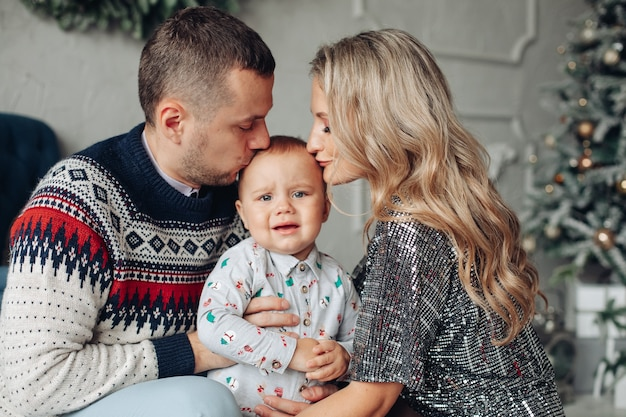 Foto de cintura para arriba de padres amorosos besando a su bebé en la cabeza con un árbol de navidad