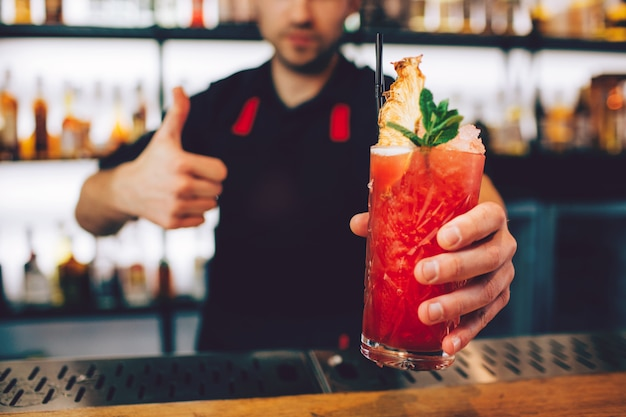 Una foto de un cóctel que es bañado por el barman. tiene un bonito color rojo. también hay un poco de hielo en la parte superior del cóctel y un trozo de menta con el túbulo del cóctel.