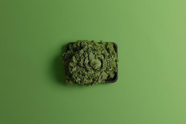 Foto de col rizada fresca cruda o ensalada cultivada en invernadero en bandeja negra aislada sobre fondo verde. concepto de cosecha, alimentación, agricultura y hortalizas. producto comestible recién cosechado
