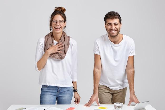 Foto de colegas felices que se regocijan en elogios del jefe por su buen trabajo, tienen sonrisas con dientes, se paran cerca del escritorio con tableta, vaso de agua y libros, aislados sobre una pared blanca