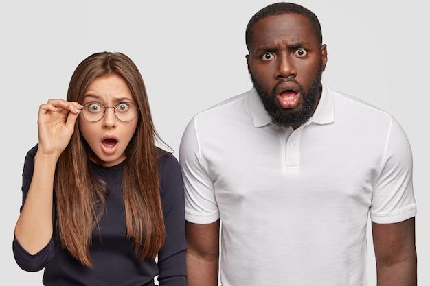 Foto de colegas de raza mixta que miran fijamente: un chico de piel oscura y una emotiva mujer caucásica no pueden creer lo que ven