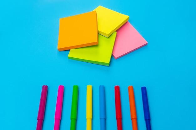 Foto de coloridos rotuladores brillantes en la parte inferior de un azul junto al cual hay un conjunto de colores amarillo, naranja, rosa y verde. de cerca. papelería. vista superior.