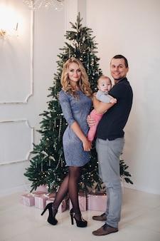 Foto de concepto de año nuevo de una familia joven feliz de dos padres y un bebé posando cerca del árbol de navidad
