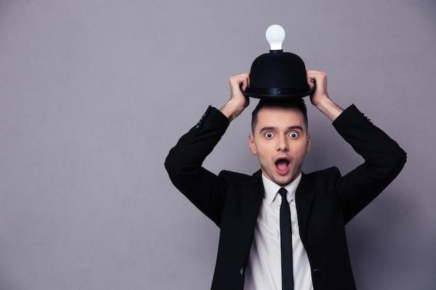 Foto de concepto de un empresario que tiene una idea sobre la pared gris