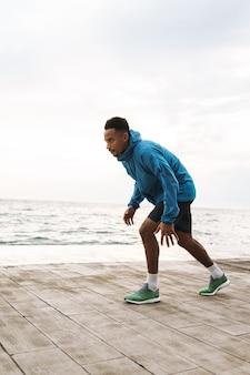 Foto de un corredor de hombre deportivo africano joven guapo fuerte al aire libre en la playa mar corriendo hacer ejercicios.