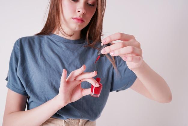 La foto de la cosecha de la muchacha adolescente linda joven pinta las uñas aisladas en gris