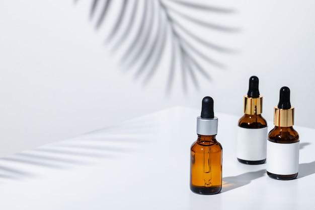 Foto creativa de botella cosmética con pipeta sobre un fondo blanco con sombra de flor tropical