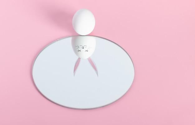 Foto creativa conceptual acerca de felices vacaciones de pascua. un huevo blanco sobre un fondo rosa se mira en el espejo y se ve reflejado con un hocico y orejas de liebre. linda cara de conejito de pascua