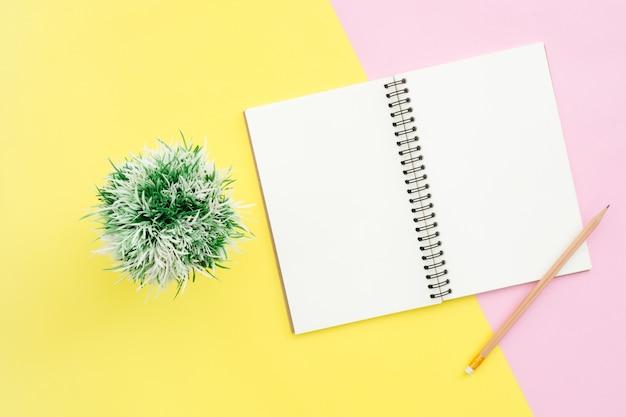 Foto creativa de la endecha plana del escritorio del espacio de trabajo. escritorio de la oficina de la vista superior con maqueta abierta cuadernos y lápiz