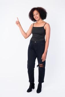 Foto de cuerpo completo de feliz joven hermosa mujer africana apuntando hacia arriba