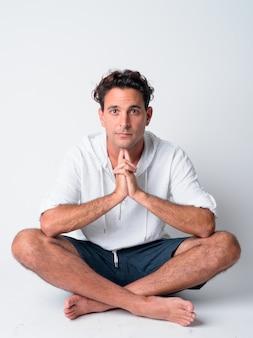 Foto de cuerpo completo de guapo hispano sentado con las piernas cruzadas