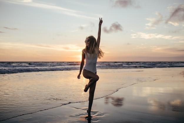 Foto de cuerpo entero de adorable chica delgada de pie sobre una pierna en la costa del océano.
