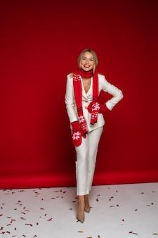 Foto de cuerpo entero de una alegre dama rubia vestida con traje blanco y guantes con bufanda mientras posa en fondo rojo.
