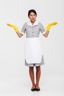 Foto de cuerpo entero de asombrada mucama en uniforme gris y guantes de goma amarillos de pie con las palmas abiertas