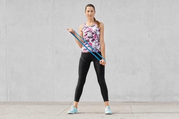 La foto de cuerpo entero de la atractiva mujer delgada en ropa deportiva hace ejercicios con el brazo con goma de mascar, usa una banda elástica para el deporte, vestida con chaleco, polainas y zapatillas de deporte, aislada sobre un muro de hormigón gris
