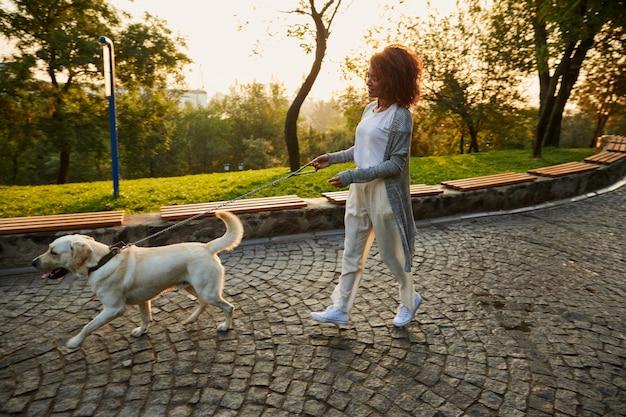 Foto de cuerpo entero de bastante saludable jovencita caminando por la mañana en el parque con perro