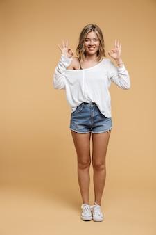 Foto de cuerpo entero de una bonita mujer caucásica de 20 años vistiendo pantalones cortos de mezclilla sonriendo y sembrando gesto ok aislado sobre pared beige