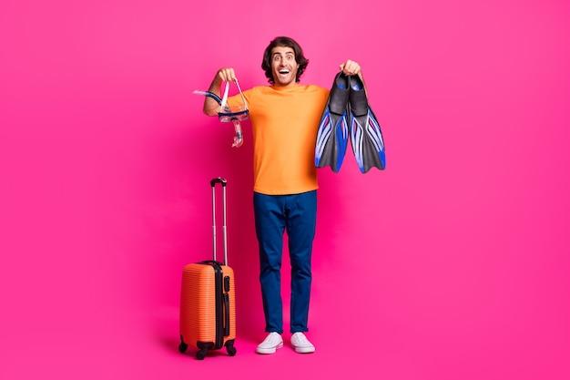 Foto de cuerpo entero de chico equipaje mostrar máscara voltea la boca abierta usar camiseta naranja jeans zapatillas aislado fondo de color rosa
