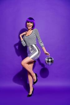 Foto de cuerpo entero de una dama encantadora con anteojos y gafas sosteniendo una bola de espejos vestida con camisa a rayas aislada sobre fondo violeta púrpura