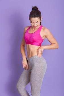Foto de cuerpo entero de deportista deportiva bien construida posando aislada sobre lila