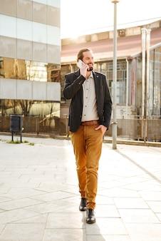 Foto de cuerpo entero de exitoso hombre corporativo o gerente de oficina en traje sonriendo, mientras camina cerca del centro de negocios y habla por teléfono celular