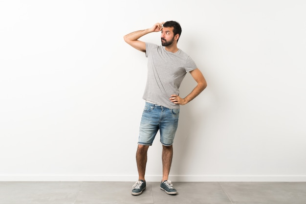 Una foto de cuerpo entero de un hombre guapo con barba que tiene dudas mientras se rasca la cabeza