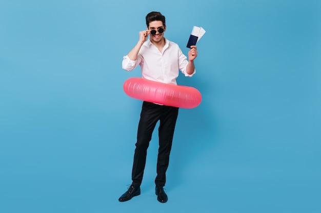 Foto de cuerpo entero de un hombre guapo en ropa de negocios con una sonrisa mirando a la cámara. chico de gafas tiene pasaporte y anillo de goma.